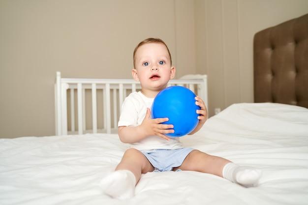 Ein kleines kind mit blauen augen hält einen ball.