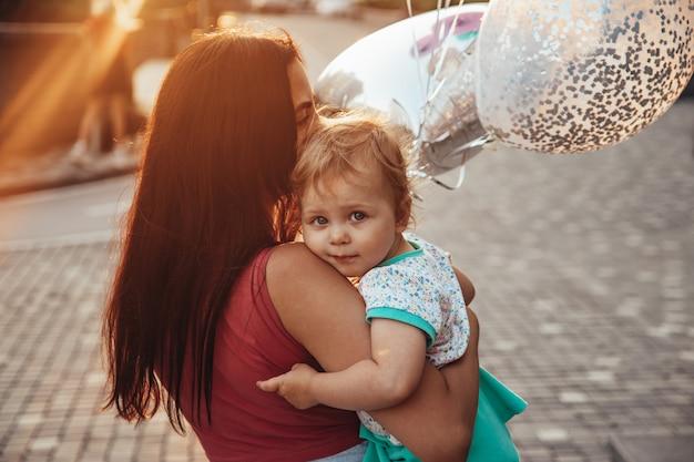 Ein kleines kind mit blauen augen in den armen ihrer mutter. luftballons und schöner sonnenuntergang.