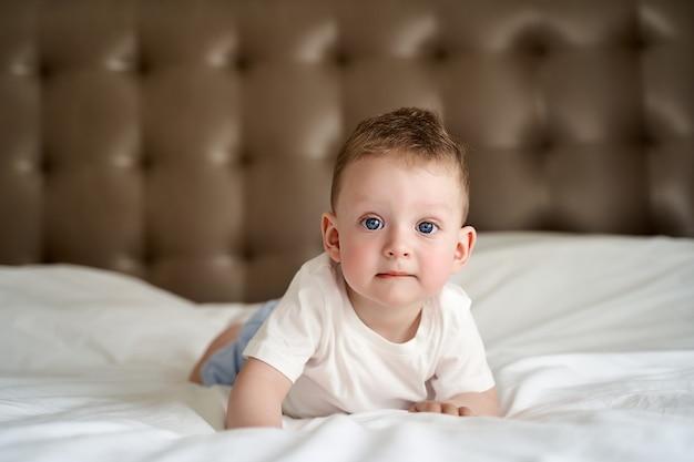Ein kleines kind mit blauen augen liegt auf einem großen bett und schaut in den rahmen.