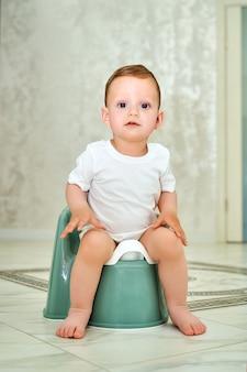 Ein kleines kind mit blauen augen sitzt auf einem töpfchen.