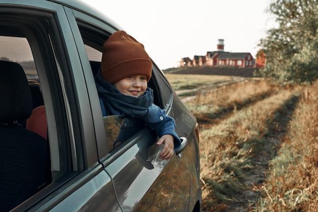 Ein kleines kind schaut aus dem offenen autofenster. leuchtturm im hintergrund. reisen mit kindern.