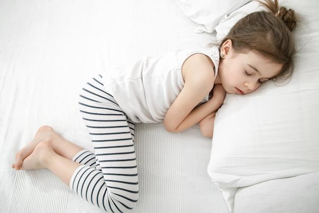 Ein kleines kind schläft im leichten schlafanzug vor dem hintergrund eines hellen bettes. baby-tagesschlaf- und gesundheitskonzept.