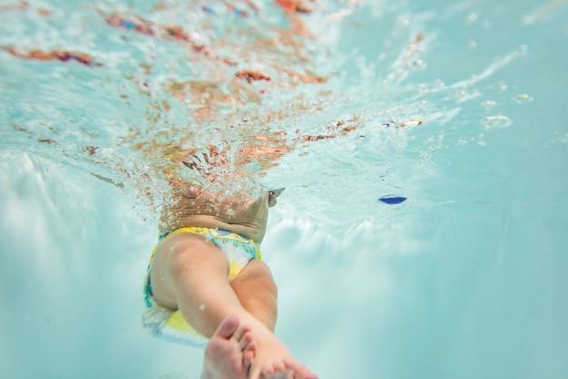 Ein kleines kind schwimmt unter wasser.
