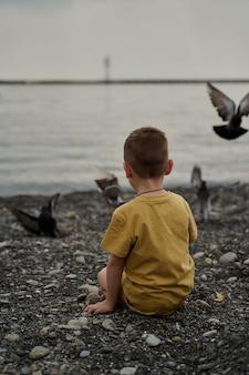 Ein kleines kind sitzt am meer und füttert tauben.