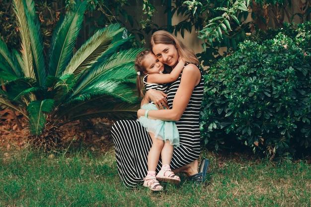 Ein kleines kind sitzt auf den händen der mutter. mamas tochter ist im urlaub. tropische blätter. reisen sie in heiße länder