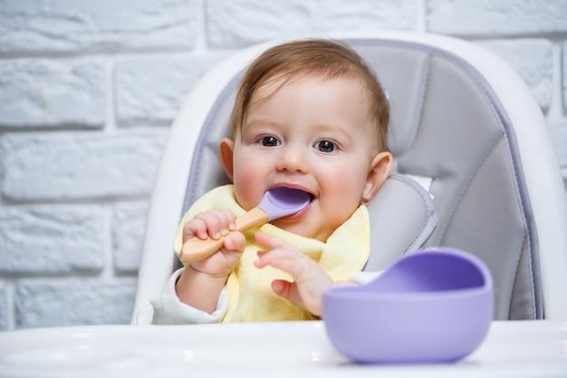 Ein kleines kind sitzt auf einem hochstuhl und isst mit einem löffel essen von einem teller. baby-silikon-utensilien zum füttern von babys
