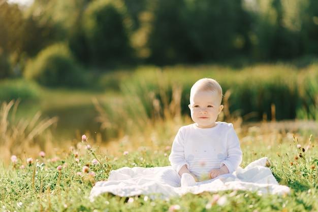 Ein kleines kind sitzt auf einer decke am ufer des sees im freien. sommerspaziergänge mit dem baby
