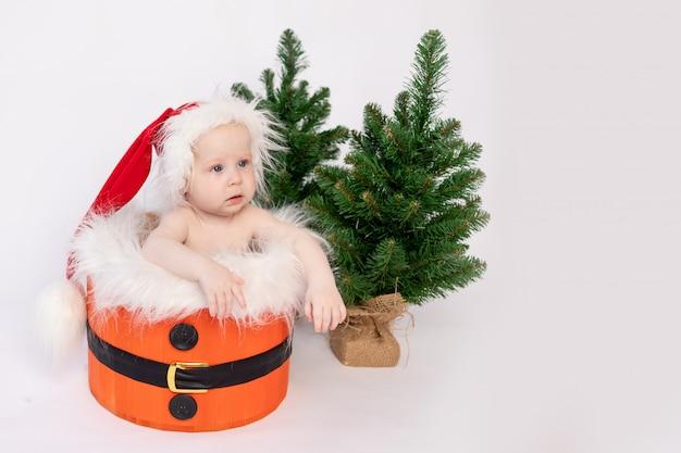 Ein kleines kind sitzt in santas korb auf einem weißen isolierten hintergrund in einem hut und mit weihnachtsbäumen, dem konzept des guten rutsch ins neue jahr und weihnachten, einem ort für text