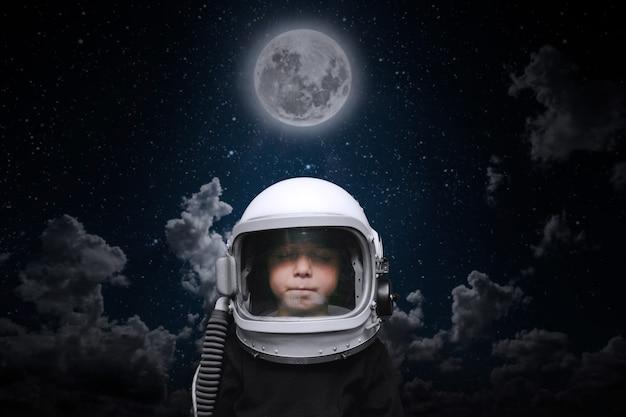 Ein kleines kind stellt sich vor, ein astronaut im helm eines astronauten zu sein. elemente dieses bildes von der nasa geliefert