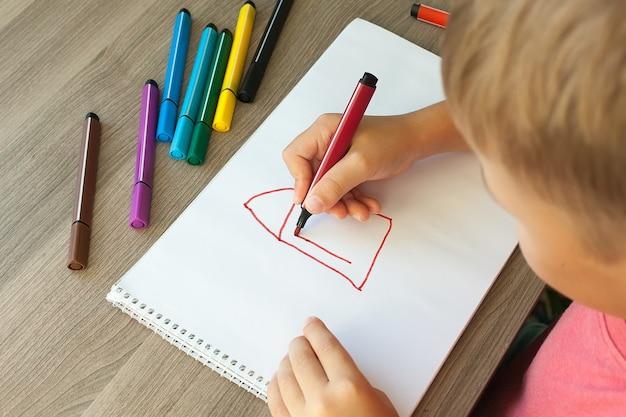 Ein kleines kind zeichnet ein haus mit markern in das album. schritt für schritt anweisungen.