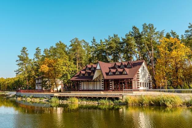 Ein kleines komplexes hotel im wald, bestehend aus mehreren häusern in kiefern am ufer des flusses. touristenurlaub