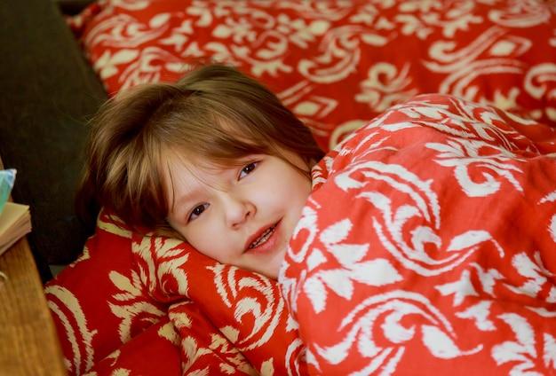 Ein kleines krankes mädchen im schlafzimmer. kleines mädchen, das auf einem bett trägt pyjamas sitzt.