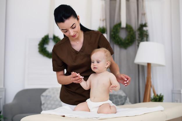 Ein kleines lustiges baby, das massage mit professioneller masseurin hat. kindermassage auf der couch in einem modernen gemütlichen raum. freundlicher und freundlicher kinderarzt.