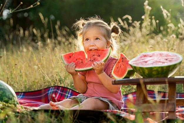 Ein kleines lustiges mädchen auf einem sommerpicknick, das reife köstliche wassermelone isst