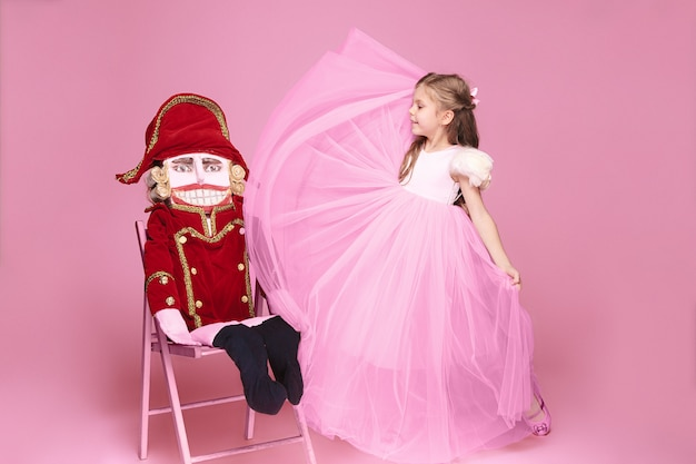 Ein kleines mädchen als schönheitsballerina am rosa langen kleid mit nussknacker am rosa studio