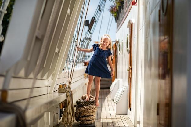 Ein kleines mädchen auf dem deck eines großen segelbootes in der stadt klaipeda.lithuania
