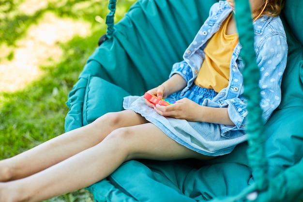 Ein kleines mädchen auf dem hängesessel im freien spielt pop it, kinderhände spielen mit buntem pop it, zappelspielzeug im hinterhof des hauses an einem sonnigen sommertag, sommerurlaub.