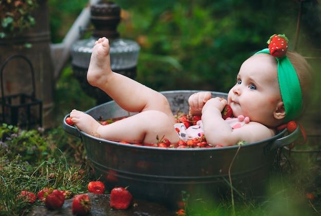Ein kleines mädchen badet in einem becken mit erdbeeren im garten.
