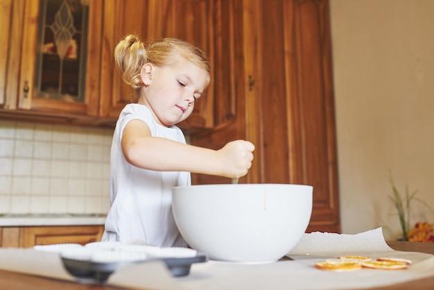 Ein kleines mädchen bereitet einen teig für muffins vor.