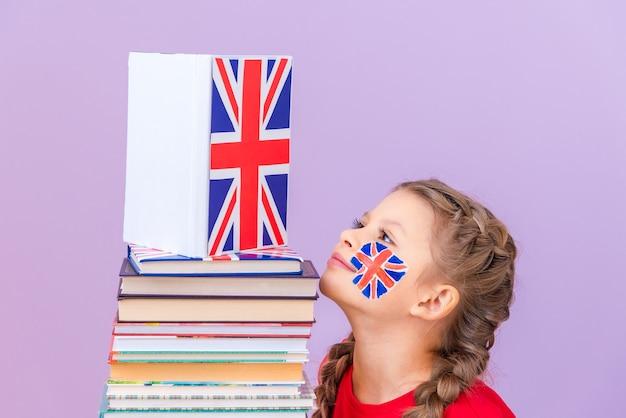 Ein kleines mädchen betrachtet einen großen gefalteten stapel bücher über die englische sprache.