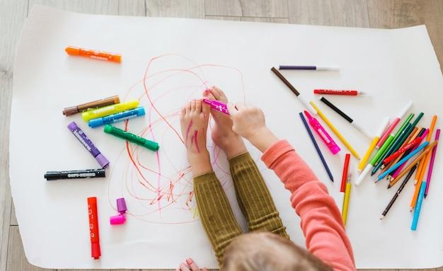 Ein kleines mädchen, das auf dem boden sitzt, genießt kreativität und zeichnet mit bleistiften, die bilder in alben ausmalen. draufsicht