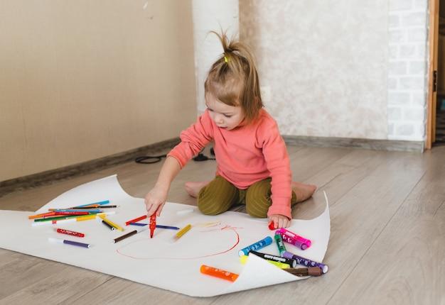 Ein kleines mädchen, das auf dem boden sitzt, genießt kreativität und zeichnet mit bleistiften, die bilder in alben ausmalen.