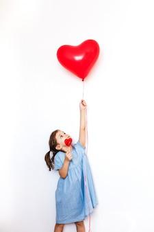 Ein kleines mädchen, das einen schönen roten herzförmigen ballon für ein valentinstaggeschenk und einen lutscher in der form eines herzens, liebhaber, valentinstag, familie und herz hält