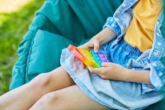 Ein kleines mädchen, das im freien auf dem hängesessel spielt, spielt pop it, kinderhände, die blasen eines regenbogen-entstressungsspielzeugs spielen, zappelspielzeug im hinterhof des hauses an einem sonnigen sommertag, sommerurlaub.