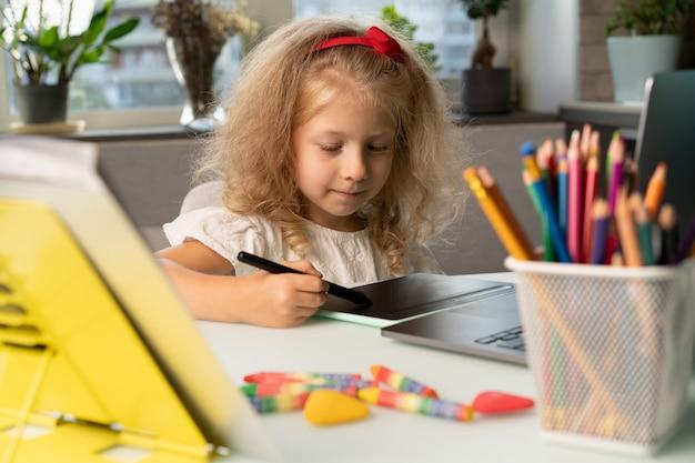 Ein kleines mädchen, das zu hause lernt, kehrt zur schule zurück, das kind zeichnet auf einem grafiktablett