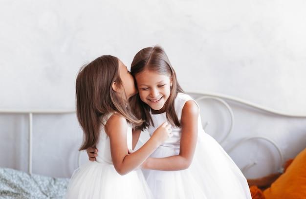 Ein kleines mädchen flüstert ihrer schwester ins ohr. zwei freundinnen in einem hellen raum