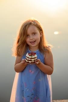 Ein kleines mädchen hält ein dessert in den händen und möchte es sehr gerne essen.