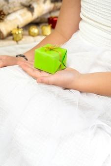 Ein kleines mädchen hält ein kleines geschenk vom weihnachtsmann in den händen