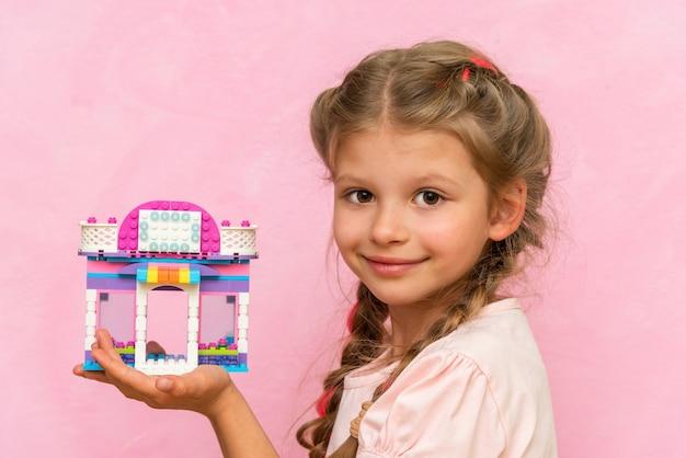 Ein kleines mädchen hält ein spielzeughaus aus würfeln.