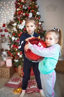 Ein kleines mädchen hält eine große rote glaskugel für den weihnachtsbaum