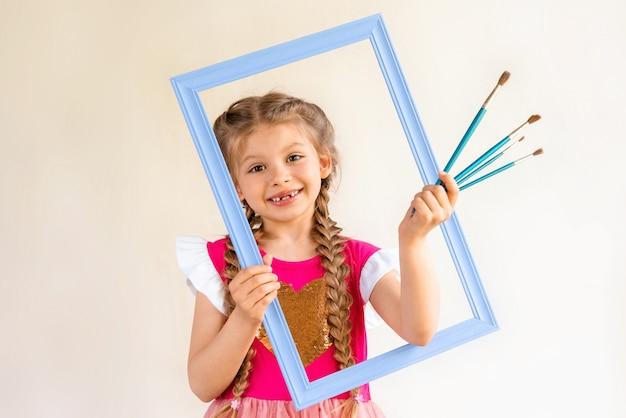 Ein kleines mädchen hält einen blauen rahmen und einen satz pinsel.