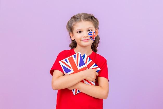 Ein kleines mädchen hält englischsprachige bücher auf einem rosafarbenen, isolierten hintergrund. schulische ausbildung.