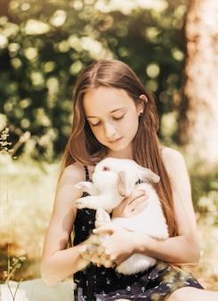 Ein kleines mädchen hält im sommer in der natur ein weißes kaninchen in den armen