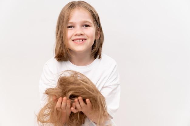 Ein kleines mädchen hält in den händen abgeschnittenes haar nach dem schneiden auf weißem hintergrund. bedeutet, kinderhaare zu pflegen. schönheitssalon für kinder.