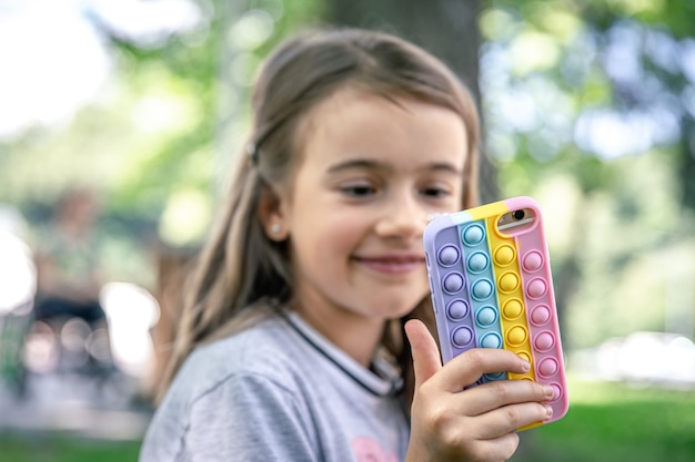 Ein kleines mädchen hält in der hand ein telefon in einer hülle mit pickeln, ein trendiges anti-stress-spielzeug.