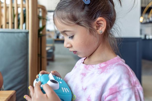 Ein kleines mädchen hält in ihren händen eine blaue spielzeug-digitalkamera für kinder zum sofortigen fotodruck.