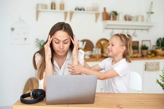 Ein kleines mädchen hindert ihre mutter daran, von zu hause aus zu arbeiten. remote-arbeit während der quarantäne. müde mutter sitzt an einem laptop und hält sich den kopf.