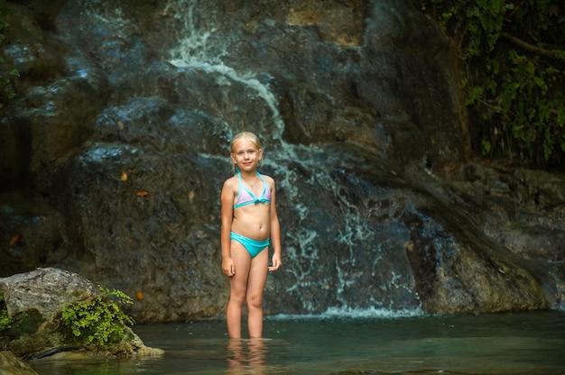 Ein kleines mädchen im badeanzug an einem wasserfall im dschungel. naturreise in der nähe eines schönen wasserfalls, türkei.