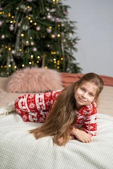 Ein kleines mädchen im schlafanzug fand am frühen morgen ein geschenk des weihnachtsmanns unter dem baum. weihnachtszaubermärchen. glückliche kindheit.