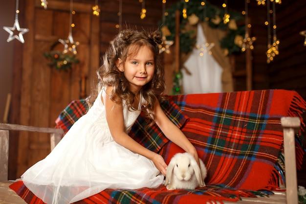 Ein kleines mädchen im weißen kleid, das auf der bank mit weißem kaninchen sitzt.
