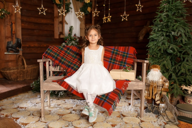 Ein kleines mädchen im weißen kleid, das auf der bank sitzt.