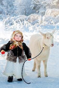 Ein kleines mädchen in alten kleidern führt eine weiße ziege an einem frostigen wintertag auf einer schneebedeckten forststraße.