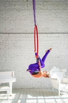 Ein kleines mädchen in der luftgymnastik beschäftigt