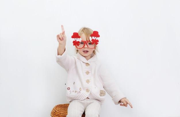 Ein kleines mädchen in der lustigen weihnachtsbrille mit schneemännern sitzt gegen eine weiße wand.