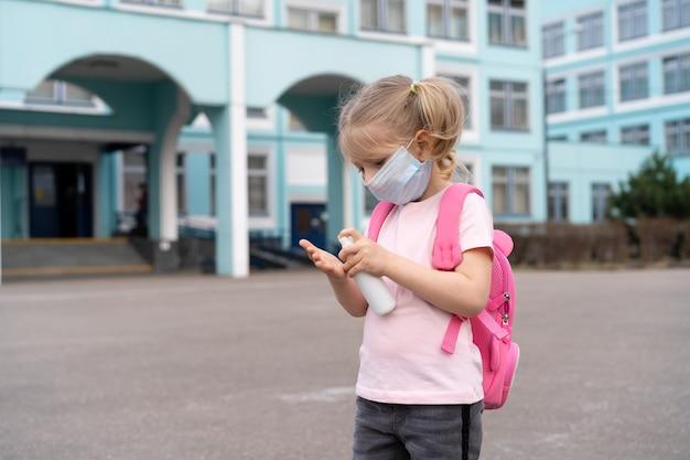 Ein kleines mädchen in der nähe der schule mit einem rucksack in einer maske und einem antiseptikum in den händen das konzept