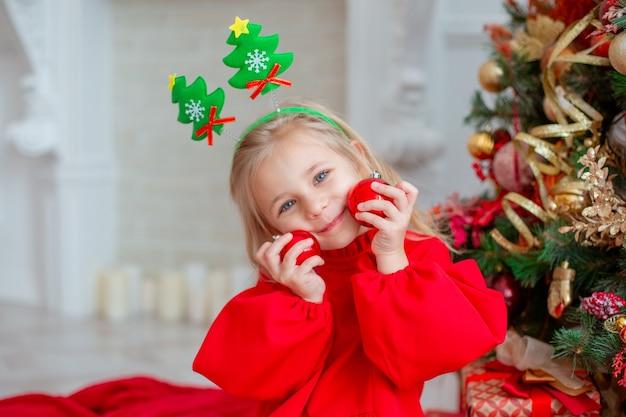 Ein kleines mädchen in der nähe des weihnachtsbaumes hält weihnachtskugeln zu hause